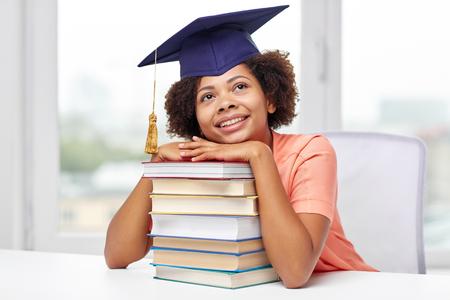 교육, 학교, 지식과 사람들이 개념 - 학술 모자 테이블에 앉아서 가정에서 꿈을 웃고있는 행복 아프리카 계 미국인 학생 소녀 미소