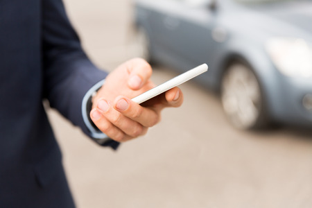 transport, business trip, technology and people concept - close up of young man hand with smartphone on car parking
