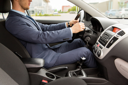 man in suit: transport, business trip, destination and people concept - close up of young man in suit driving car