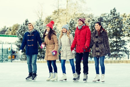 patinaje sobre hielo: gente, invierno, la amistad, el deporte y el ocio concepto - amigos felices de patinaje sobre hielo y de la mano en pista al aire libre