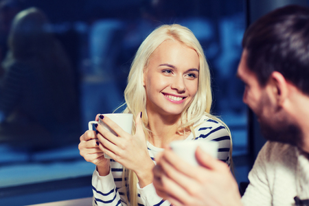 talking people: people, leisure, communication, eating and drinking concept - happy couple meeting and drinking tea or coffee at cafe