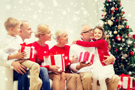 family couch: family, holidays, generation, christmas and people concept - smiling family with gift boxes sitting on couch and hugging at home
