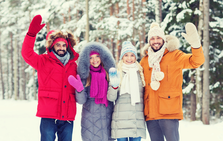 couples outdoors: love, relationship, season, friendship and people concept - group of smiling men and women waving hands in winter forest