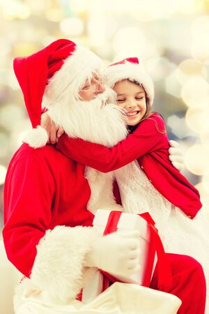 hug: holidays, christmas, childhood and people concept - smiling little girl hugging with santa claus over lights background