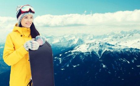 sport and leisure: winter, leisure, sport and people concept - happy young woman in ski goggles with snowboard over snowy mountain background