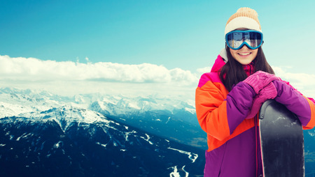 winter, leisure, sport and people concept - happy young woman in ski goggles with snowboard over snowy mountain background
