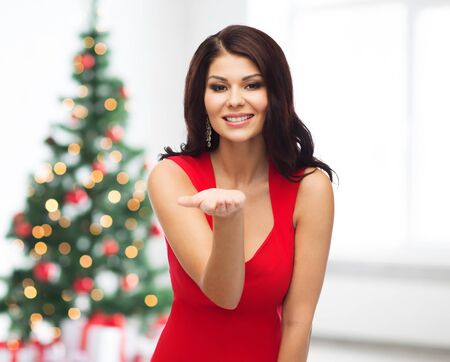 empty of people: people, holidays and advertisement concept - beautiful sexy woman in red dress showing something on empty hand over room with christmas tree and gifts background Stock Photo