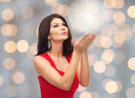 gente, fiestas, la navidad, la magia y el concepto de moda - hermosa mujer sexy en vestido rojo sopla polvo de hadas sobre luces de fondo