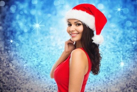 sexy glamour: people, holidays, christmas and celebration concept - beautiful sexy woman in santa hat and red dress over blue glitter or lights background