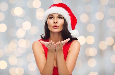 hot girl nude: people, holidays, christmas and celebration concept - beautiful sexy woman in santa hat and red dress sending blow kiss over holidays lights background Stock Photo