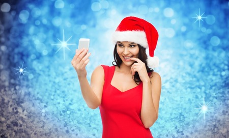 sexy young girl: people, holidays, christmas and technology concept - beautiful sexy woman in red santa hat taking selfie picture by smartphone over blue glitter or lights background Фото со стока