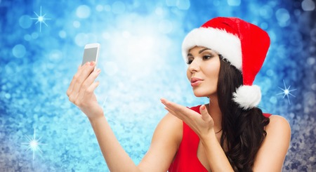 hispanic woman: people, holidays, christmas and technology concept - beautiful sexy woman in red santa hat taking selfie picture by smartphone and sending blow kiss to camera over blue glitter or lights background