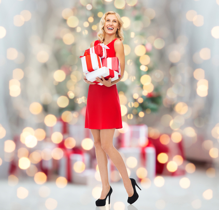 red dress: people, christmas, birthday and holidays concept - happy young woman in red dress holding gift boxes over christmas tree lights background