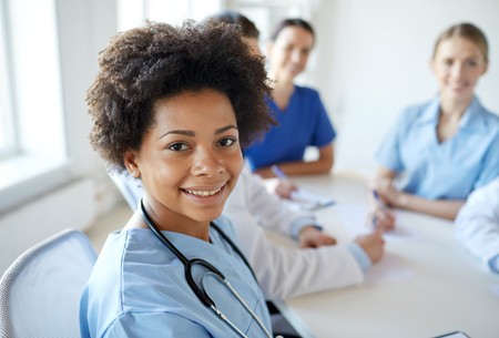 gezondheidszorg, beroep, mensen en geneeskunde concept - gelukkig African American vrouwelijke arts of verpleegkundige via groep van artsen bijeen in het ziekenhuis