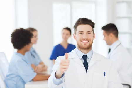 medics: clinic, profession, people and medicine concept - happy male doctor over group of medics meeting at hospital showing thumbs up gesture Stock Photo