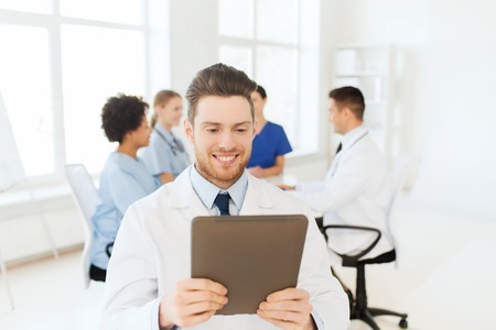 medics: clinic, profession, people and medicine concept - happy male doctor with tablet pc computer over group of medics meeting at hospital