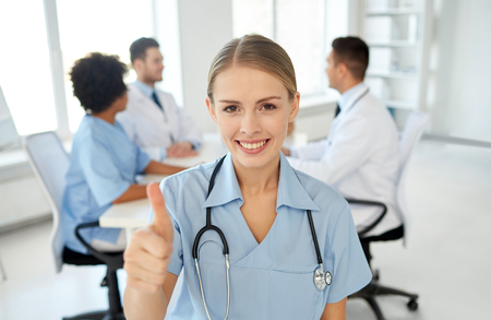 medics: health care, gesture, profession, people and medicine concept - happy female doctor or nurse over group of medics meeting at hospital showing thumbs up gesture