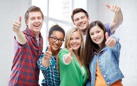 교육, 사람, 우정과 학습 개념 - 엄지 손가락을 보여주는 행복 국제 고등학교 학생이나 친구들의 그룹