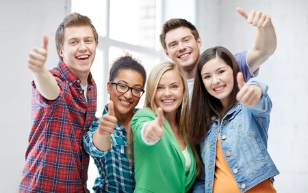 onderwijs, mensen, vriendschap en leren concept - groep gelukkige internationale middelbare scholieren of klasgenoten zien thumbs up