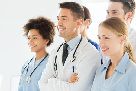 educator: hospital, profession, people and medicine concept - group of happy doctors wit stethoscopes or mentor with interns at hospital Stock Photo