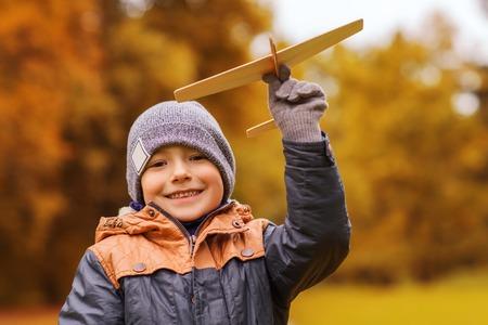herfst, jeugd, droom, vrije tijd en mensen concept - gelukkig jongetje spelen met houten speelgoed vliegtuig in openlucht Stockfoto