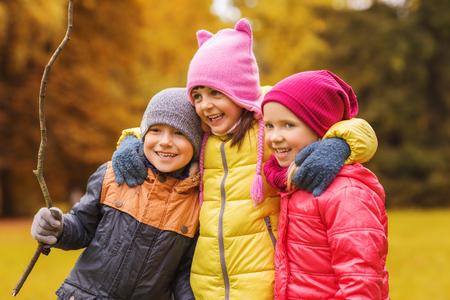 familias jovenes: la infancia, el ocio, la amistad y el concepto de la gente - grupo de niños felices que abrazan en parque del otoño Foto de archivo