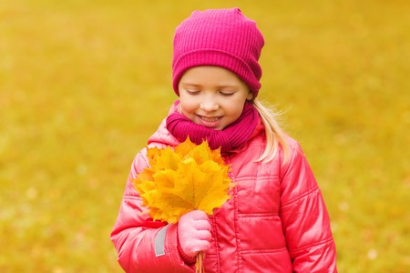 beautiful preteen girl: autumn, childhood, happiness and people concept - happy beautiful little girl with maple leaves bunch outdoors