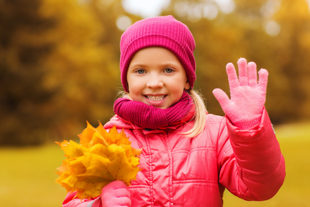 happy little girl: autumn, childhood, happiness and people concept - happy beautiful little girl with maple leaves bunch waving hand outdoors