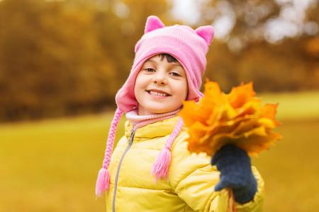 jolie fille: l'automne, l'enfance, le bonheur et les gens concept - heureux belle petite fille de feuilles d'�rable tas ext�rieur