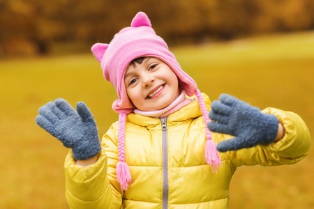 animal beautiful: autumn, childhood, happiness and people concept - happy beautiful little girl waving hands outdoors Stock Photo