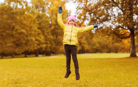 cute little girl: autumn, childhood, happiness and people concept - happy little girl with raised hands jumping and having fun outdoors