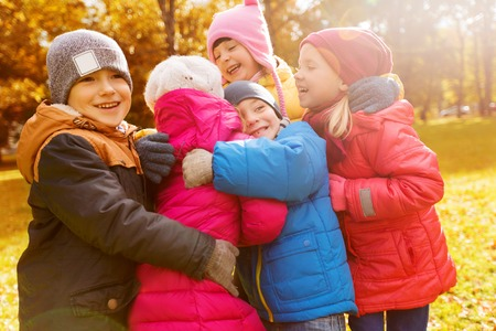 young man smiling: childhood, leisure, friendship and people concept - group of happy kids hugging in autumn park