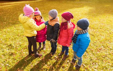 lider: la infancia, el ocio, la amistad y el concepto de la gente - grupo de niños felices en el conteo parque del otoño y la elección de líder del juego Foto de archivo