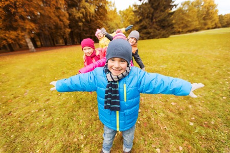group of young people: autumn, childhood, leisure and people concept - group of happy little children playing planes outdoors