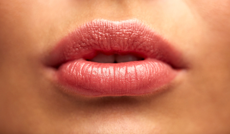 augmentation: beauty, people, make-up, plastic surgery and cosmetics concept - close up of young woman lips