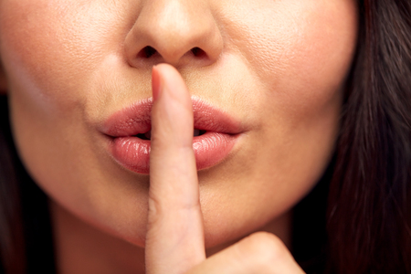 shush: silence, gesture and beauty concept - close up of young woman holding finger on lips