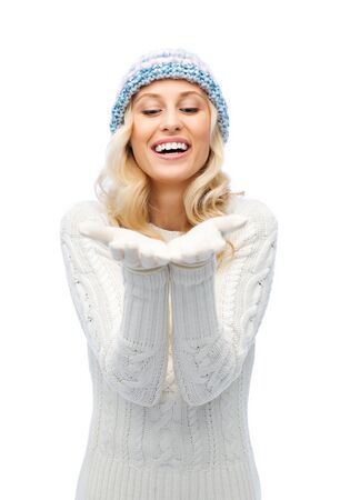 empty of people: winter, advertisement, christmas and people concept - smiling young woman in winter hat and sweater holding something on her empty palms Stock Photo
