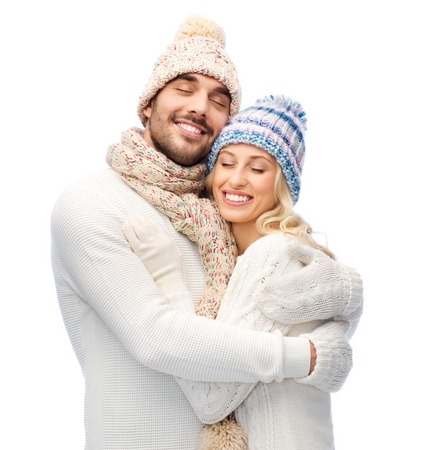 winter fashion: winter, fashion, couple, christmas and people concept - smiling man and woman in hats and scarf hugging