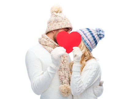 caras felices: love, valentines day, couple, christmas and people concept - smiling man and woman in winter hats and scarf hiding behind red paper heart shape Foto de archivo