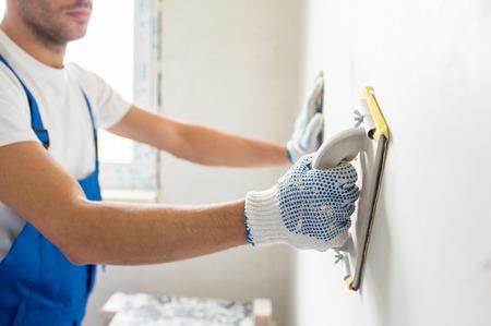 la construcción, la profesión y la gente concepto - cerca de la pared interior masculina constructor de lijado