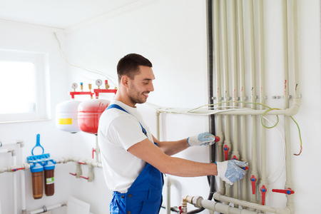 building, profession and people concept - builder or plumber working with water pipes in boiler room Standard-Bild