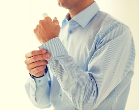 man shirt: people, business, fashion and clothing concept - close up of man fastening buttons on shirt sleeve at home
