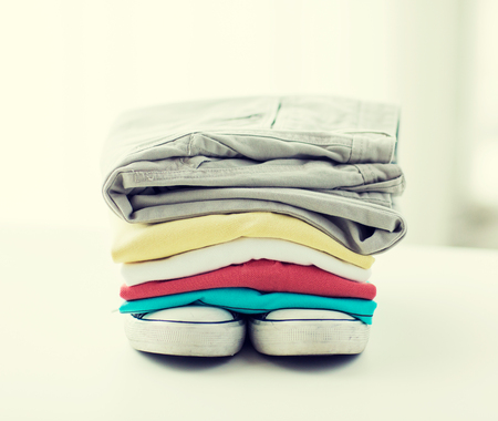 folded: clothes, personal staff and objects concept - close up of folded shirts, pants and shoes on table at home Stock Photo