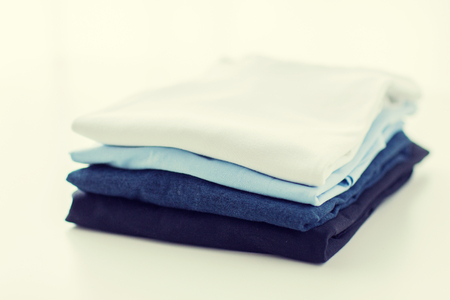 ironed: ironing, laundry, clothes, housekeeping and objects concept - close up of ironed and folded t-shirts on table at home Stock Photo