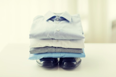 ironed: business, style, clothes, housekeeping and objects concept - close up of ironed and folded shirts and formal shoes on table at home Stock Photo