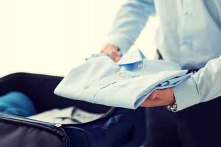 folded hands: business, trip, luggage and people concept - close up of businessman packing clothes into travel bag Stock Photo