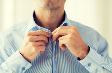 formal dressing: people, business, fashion and clothing concept - close up of man dressing up and fastening buttons on shirt at home