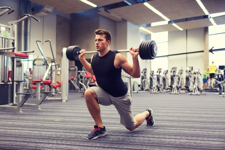 barbell: sport, bodybuilding, lifestyle and people concept - young man with barbell flexing muscles and making shoulder press lunge in gym Stock Photo