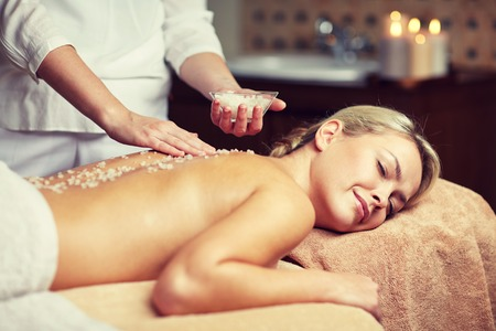 relaxed woman: people, beauty, spa, massage and relaxation concept - close up of beautiful young woman lying with closed eyes and therapist holding salt bowl in spa