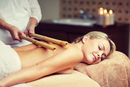relaxation massage: people, beauty, spa, healthy lifestyle and relaxation concept - close up of beautiful young woman lying with closed eyes and having bamboo massage in spa